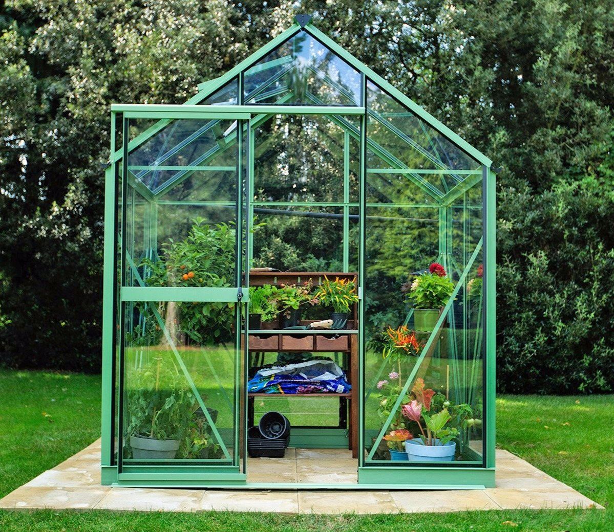 An Evika greenhouse in pale green colour finish.