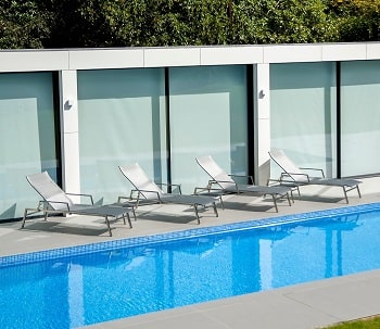 Four Alexander Rose Cologne sun Bed set out by the pool for illustration purposes.