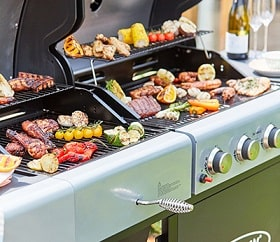 The grill of an open gas barbeque filled with various foods