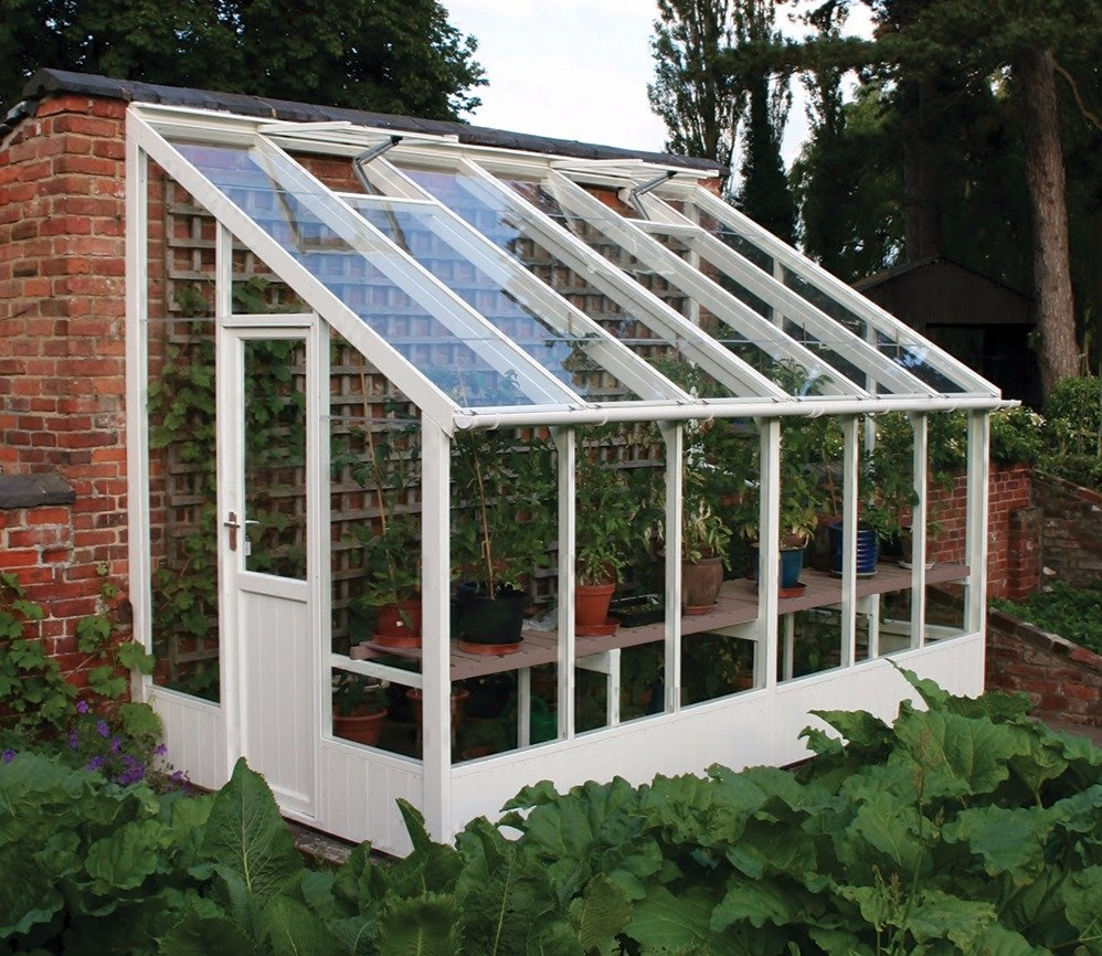 A painted wooden greenhouse in white.