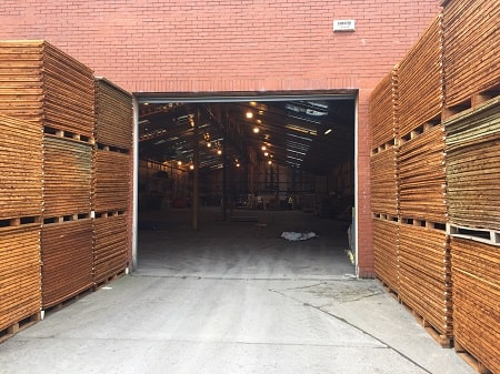 Pallets of timber leading to a warehouse