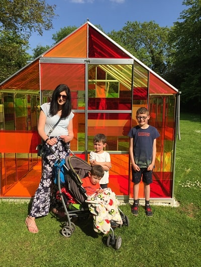 A mother and her 3 children smiling in front of a multi-coloured acrylic panelled greenhouse