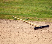 a rake on the ground surrounded by stones.