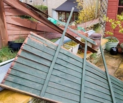 Fallen garden fence due to storm and extreme winds.