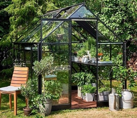 A contemporary Qube Greenhouse with a black, powder-coated aluminium frame, stocked with plants